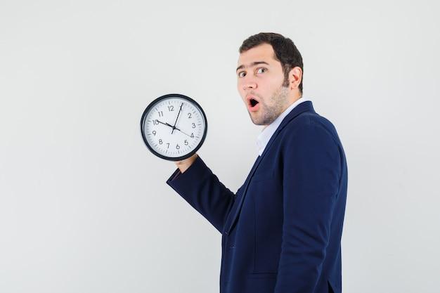 Jovem macho segurando o relógio de parede com camisa e jaqueta e parecendo surpreso. .