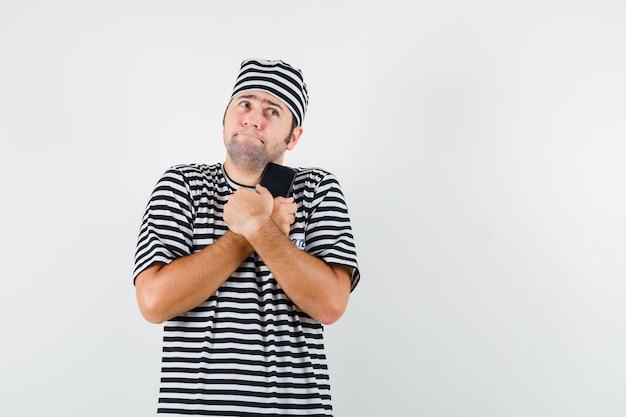 Jovem macho segurando o telefone móvel em t-shirt, chapéu e parecendo confuso, vista frontal.