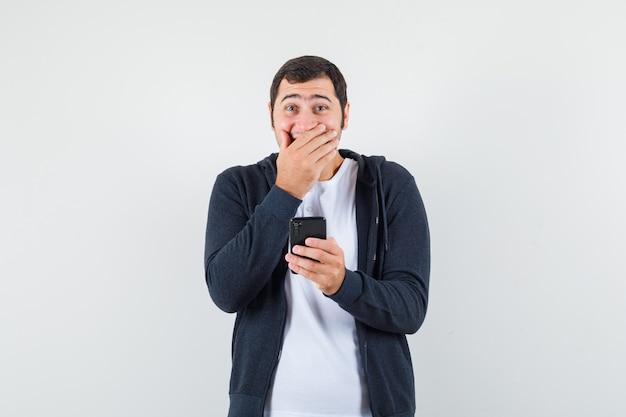 Jovem macho segurando o telefone móvel em t-shirt, jaqueta e parecendo feliz. vista frontal.