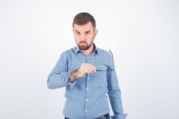 Jovem macho segurando óculos enquanto olha para a câmera em camiseta, jeans e bonito. vista frontal.