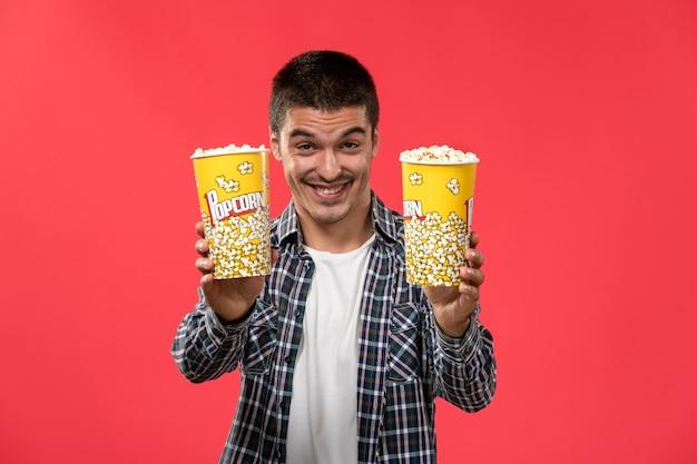 Jovem macho segurando pacotes de pipoca e sorrindo em um filme de cinema com parede vermelha clara