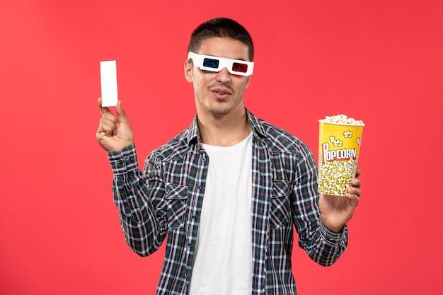 Jovem macho segurando pipoca e bilhete em óculos de sol de frente no filme de cinema de parede vermelha