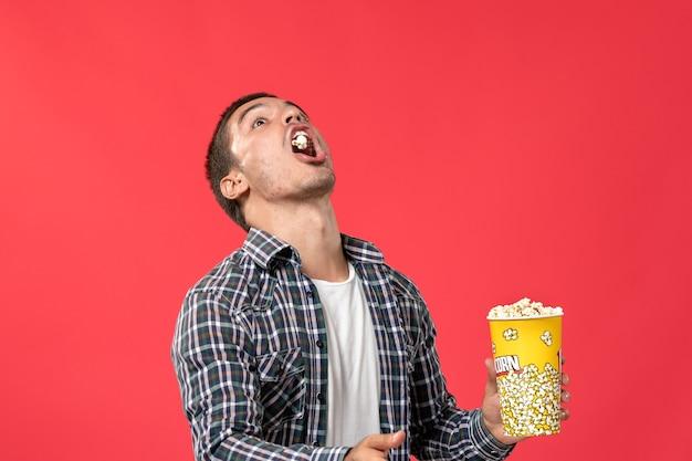 Jovem macho segurando pipoca e pegando-a com a boca na parede vermelha filme cinema teatro filme
