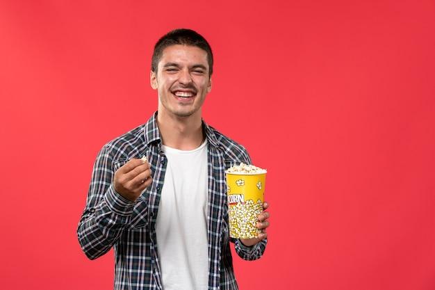 Jovem macho segurando pipoca e rindo em um filme de cinema com parede vermelha clara