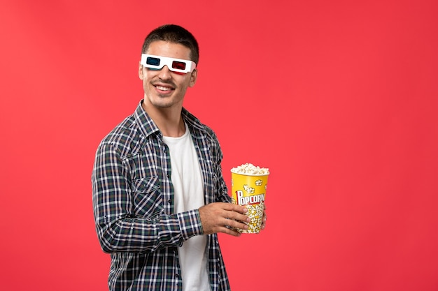 Jovem macho segurando pipoca em óculos de sol -d na parede vermelha cinema filme de cinema