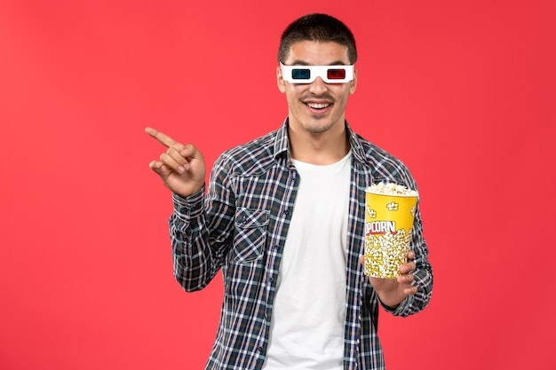 Jovem macho segurando pipoca em óculos de sol -d no filme de cinema de parede vermelha clara