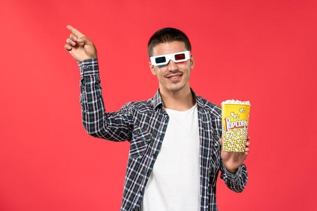 Jovem macho segurando pipoca em óculos de sol na parede vermelha filme de cinema.