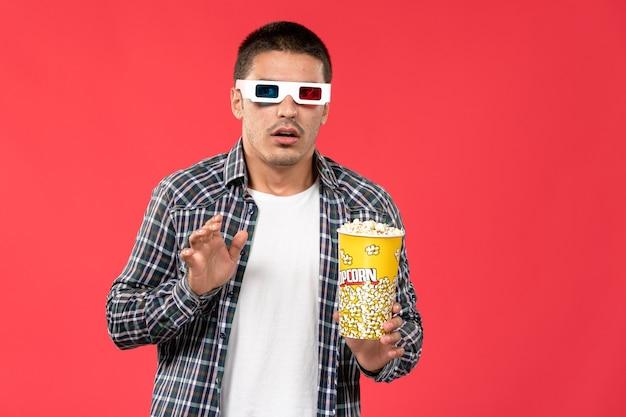 Jovem macho segurando pipoca em óculos de sol sobre a parede vermelha-claro filme masculino teatro cinema cinema
