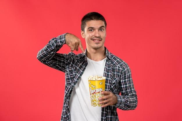Jovem macho segurando pipoca em uma parede vermelha-clara filme de cinema masculino teatro