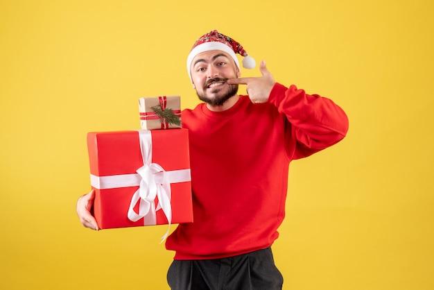Jovem macho segurando presentes de natal em fundo amarelo