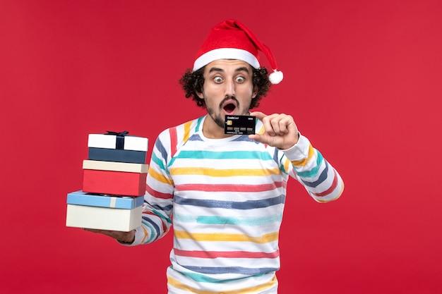 Jovem macho segurando presentes e cartão do banco na parede vermelha dinheiro de ano novo masculino vermelho