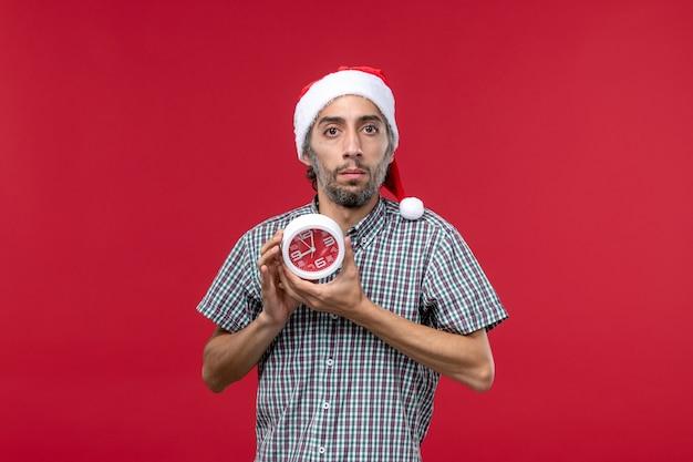 Jovem macho segurando relógios redondos no fundo vermelho