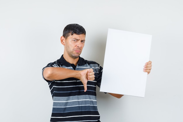 Jovem macho segurando um cartaz em branco com o polegar para baixo na t-shirt e olhando subjugado, vista frontal.