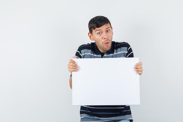 Jovem macho segurando um cartaz em branco na camiseta e parece feliz. vista frontal.