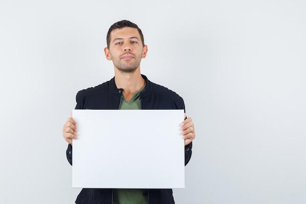 Jovem macho segurando um cartaz em branco na t-shirt, jaqueta e parecendo sensato. vista frontal.