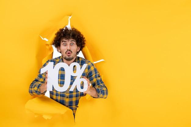 Jovem macho segurando um fundo amarelo