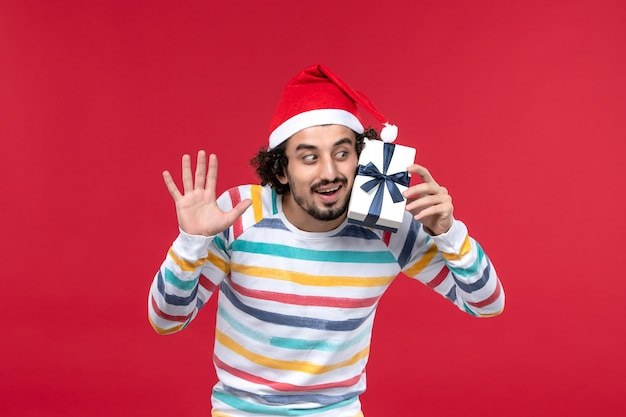 Jovem macho segurando um pequeno presente em um fundo vermelho, feriado vermelho, emoção de ano novo