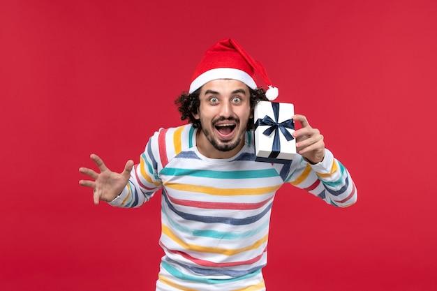 Jovem macho segurando um pequeno presente sobre fundo vermelho emoções vermelhas feriado de ano novo