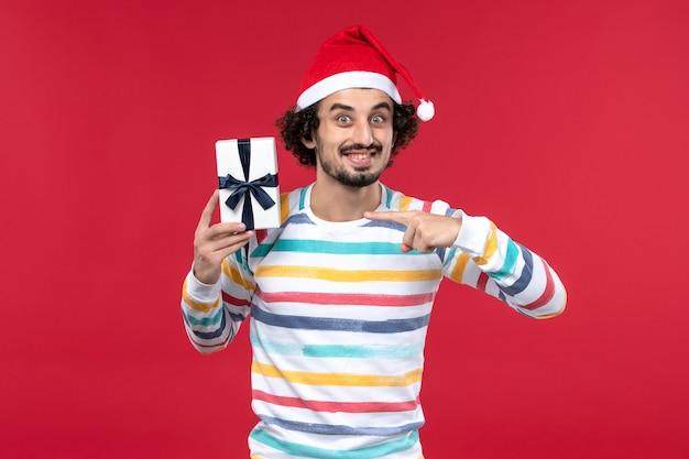 Jovem macho segurando um presentinho em um fundo vermelho, vermelho, feriados, emoções de ano novo, vista frontal