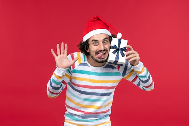 Jovem macho segurando um presentinho sobre fundo vermelho emoções vermelhas feriados ano novo