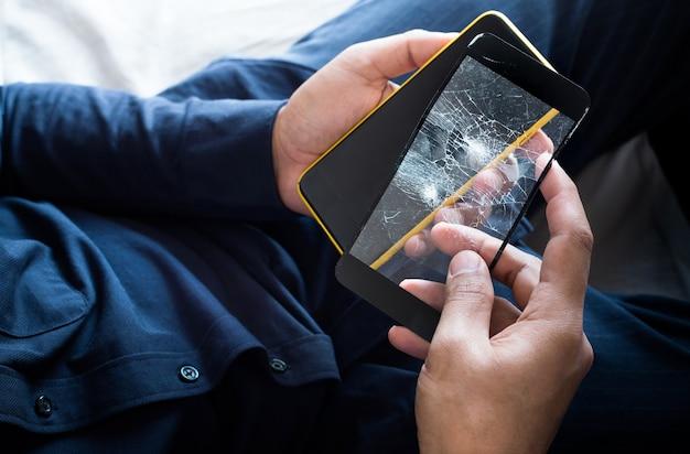Jovem macho segurando um smartphone e uma proteção de tela de filme de vidro quebrado quebrada e acessório