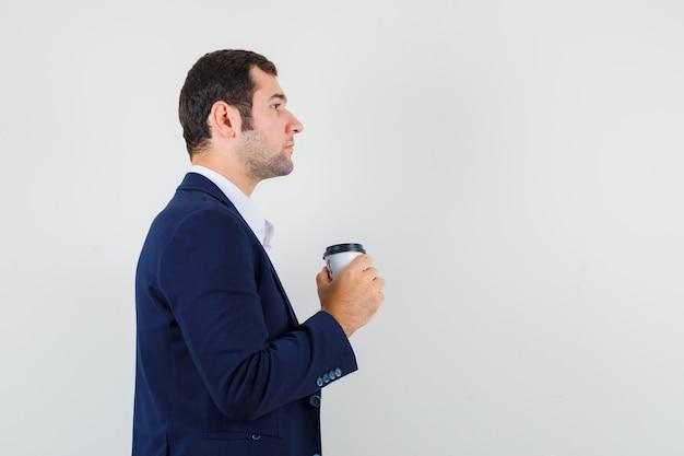 Jovem macho segurando uma xícara de café com uma camisa, jaqueta e olhando focado