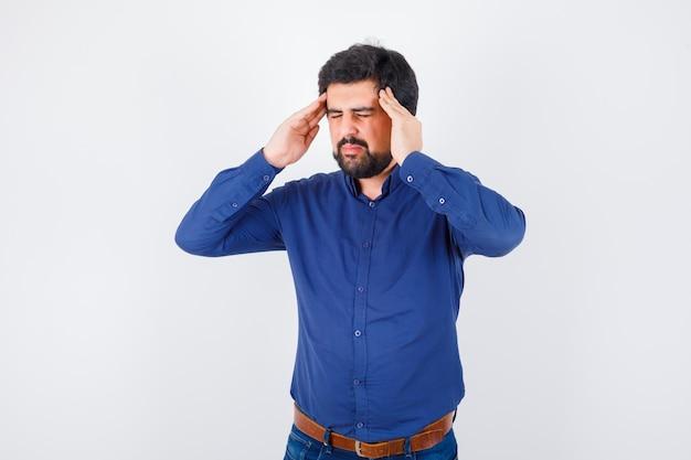 Jovem macho sofrendo de dor de cabeça, camisa azul e parecendo cansado, vista frontal.