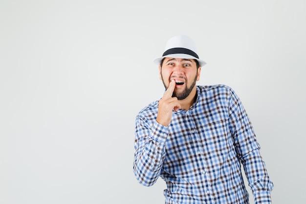 Jovem macho sofrendo de dor de dente dolorosa, vestindo camisa quadriculada, chapéu e parecendo desconfortável. vista frontal.