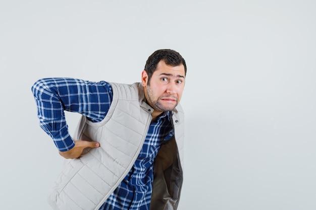 Jovem macho sofrendo de dor na cintura na camisa, jaqueta sem mangas e parecendo preocupado, vista frontal.