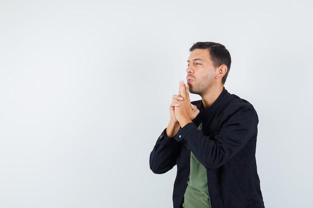 Jovem macho soprando em arma feita por mãos em t-shirt, jaqueta, vista frontal.