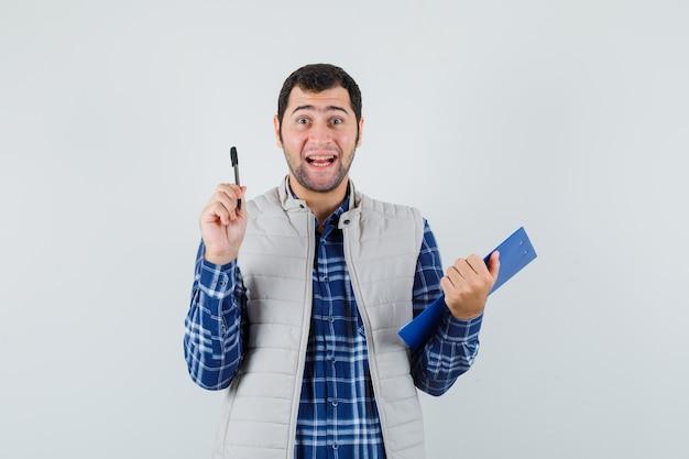 Jovem macho sorrindo enquanto segura a caneta e o caderno na camisa, jaqueta e olhando feliz, vista frontal.