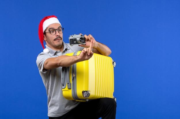 Jovem macho tirando foto e segurando a sacola em aviões de férias com parede azul