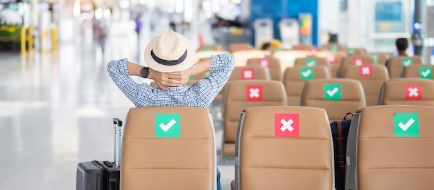Jovem macho usa máscara facial sentado na cadeira no terminal do aeroporto, infecção por doença de coronavirus (covid-19), viajante moderno pronto para viajar. novos conceitos de normal e distanciamento social