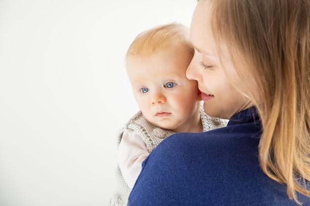 Jovem mãe abraçando criança infantil fofa