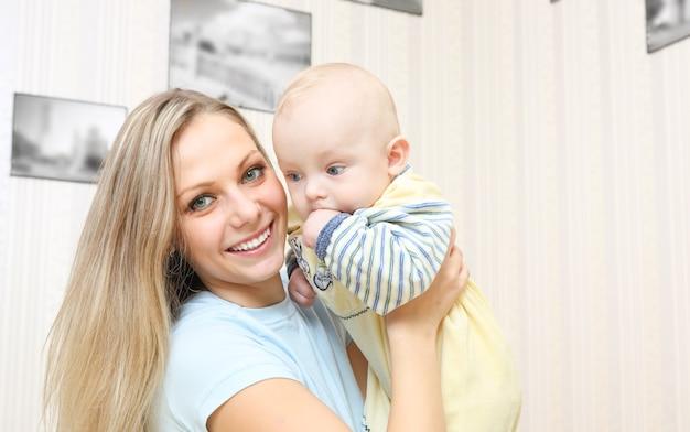 Jovem mãe abraçando o bebê em casa
