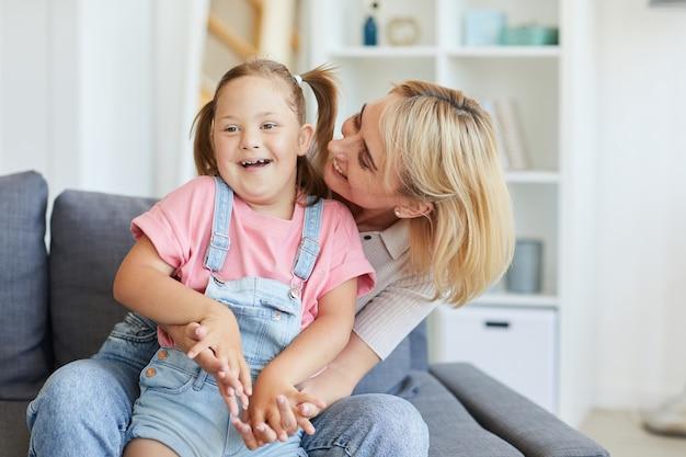 Jovem mãe abraçando seu filho deficiente enquanto eles estão sentados no sofá da sala