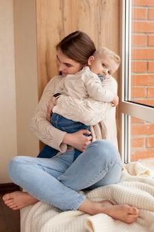 Jovem mãe abraçando seu filho