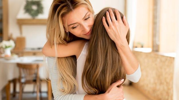Jovem mãe abraçando sua doce filha