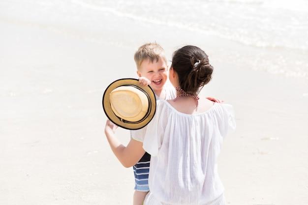 Jovem mãe abraçar seu filho criança nas férias de verão