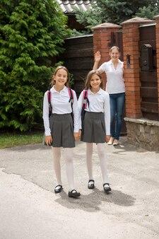 Jovem mãe acenando com a mão para as filhas caminhando para a escola