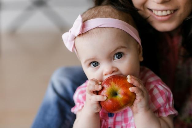 Jovem mãe adorável, rindo, abraçando a filha sorridente e fofa criança engraçada curtindo o tempo juntos em casa
