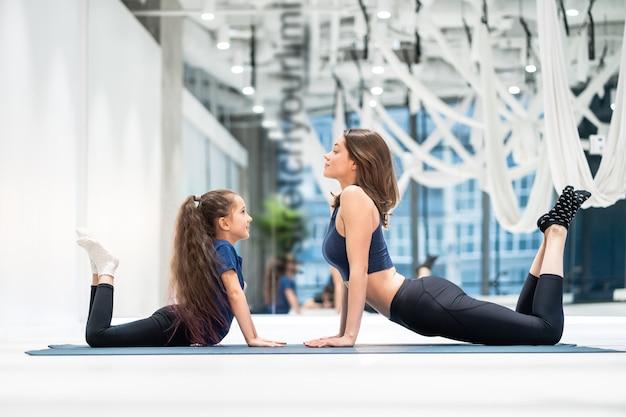 Jovem mãe adulta e filha junto em aeróbica