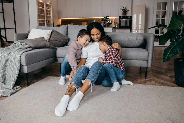 Jovem mãe afro-americana abraça seus amados filhinhos com ternura