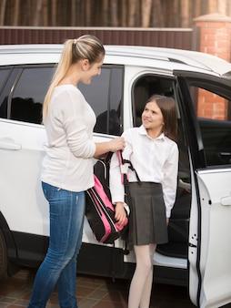 Jovem mãe ajudando a filha a sair do carro e colocar a mochila escolar