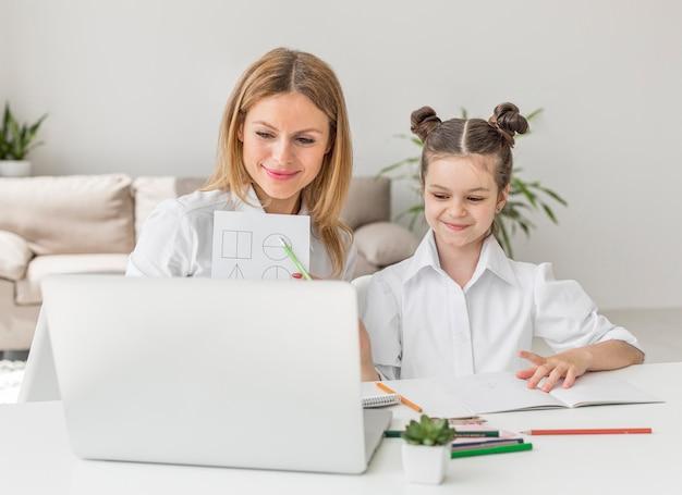 Jovem mãe ajudando a filha em uma aula on-line