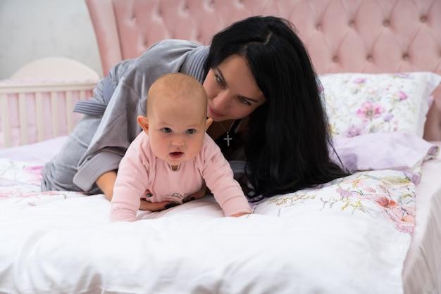 Jovem mãe ajudando seu bebê a engatinhar, deitada na cama com ela e segurando-a com a mão