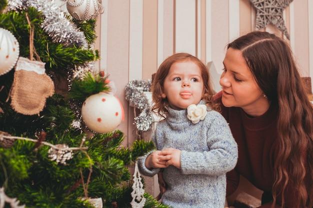 Jovem mãe ajudando sua filha a decorar a árvore de natal