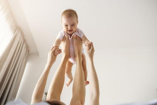 Jovem mãe alegre brincando com seu bebê recém-nascido, deitado na cama em casa.