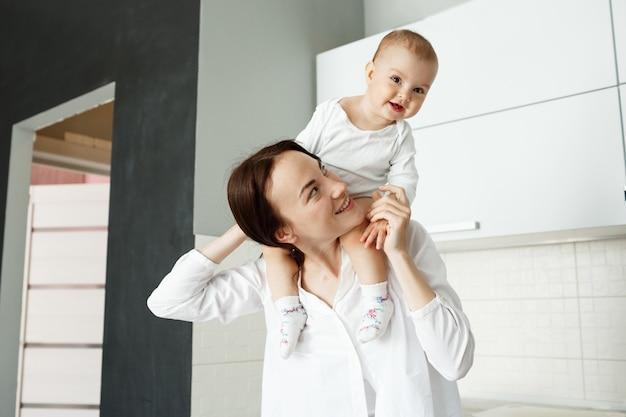 Jovem mãe alegre carregando seu bebê nos ombros e rindo
