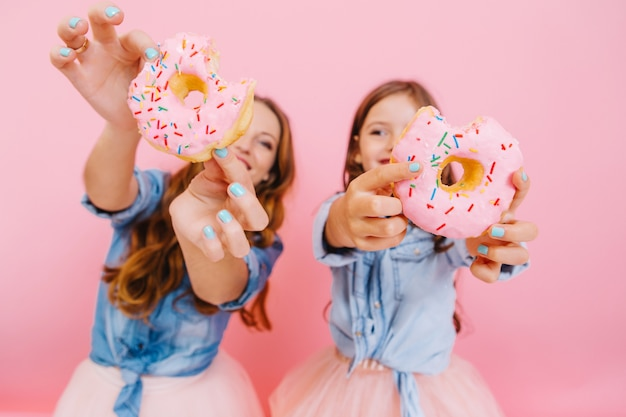 Jovem mãe alegre e linda filha sorridente se divertindo com saborosos donuts esperando a festa do chá com a família. menina com a mãe mostrando rosquinhas que eles cozinharam juntas e rindo